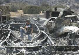 Lucas Martin stares at all that remains of his fire ravaged home in South Lake, Calif., Sunday, June 26, 2016. Martin's home was among the more than 200 homes and buildings destroyed by the fire that swept through the area near Lake Isabella, Calif. (AP Photo/Rich Pedroncelli)