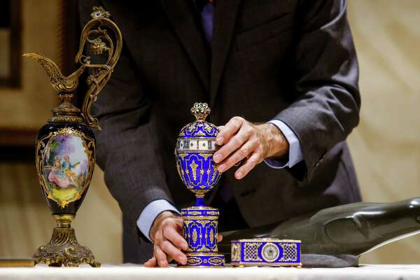 "Gary Piattoni, one of the hosts of PBS's ""Antiques Roadshow,"" examines a clock he thinks could possibly be an authentic Fabergé."