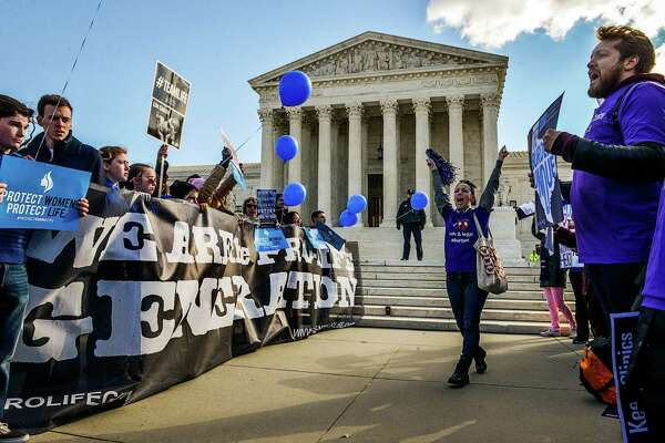 Antiabortion demonstrators and abortion rights supporters face off outside the Supreme Court in March. On Monday, the court ruled against the Texas restrictions involved.
