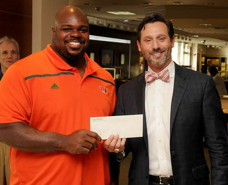 Brad Marks presents the check to Vince Wilfork at the Men's Night Out event at I.W. Marks Jewelers Wednesday June 15,2016.(Dave Rossman Photo)
