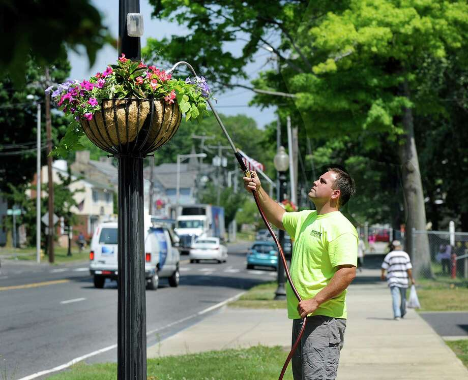 """Brian Kolwicz, owner of Kolwicz Landscaping, waters the flowers baskets along Main Street in Danbury Monday, June 27, 2016. He says he waters the pots two-three times a week """"when it's dry like this,"""" adding """" I haven't seen a June like this in quite some time."""" Photo: Carol Kaliff / The News-Times"""