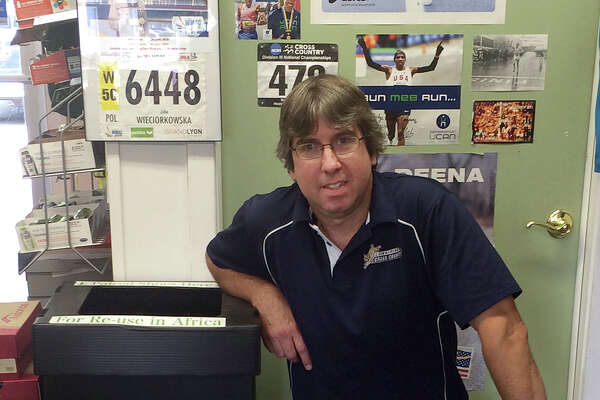 Chris Dickinson of Woodbridge Running Company kneels by one of the collection boxes for old shoes to be donated the Rerun Shoes program.