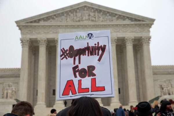 A sign in favor of affirmative action is held up outside of the Supreme Court in Washington, in December, as the court heard  the Fisher v. University of Texas at Austin affirmative action case. The court on Thursday ruled to uphold UT's use of race in its admission policies.