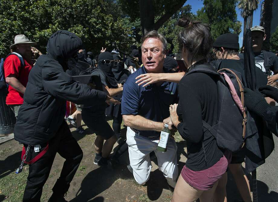 KCRA television reporter Mike Luery runs away from members of the group called ANTIFA Sacramento (Anti-Fascism Action), who are staging a counter-protest against the Traditionalist Worker Party and the Golden State Skinheads, at the California state Capitol in Sacramento, Calif., Sunday, June 26, 2016. Several people were stabbed Sunday when counter-protesters clashed with members of right-wing extremists groups that planned to hold a rally outside the Capitol building, authorities said. (Paul Kitagaki Jr./The Sacramento Bee via AP) MANDATORY CREDIT Photo: Paul Kitagaki Jr., Associated Press
