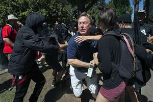 KCRA television reporter Mike Luery runs away from members of the group called ANTIFA Sacramento (Anti-Fascism Action), who are staging a counter-protest against the Traditionalist Worker Party and the Golden State Skinheads, at the California state Capitol in Sacramento, Calif., Sunday, June 26, 2016. Several people were stabbed Sunday when counter-protesters clashed with members of right-wing extremists groups that planned to hold a rally outside the Capitol building, authorities said. (Paul Kitagaki Jr./The Sacramento Bee via AP) MANDATORY CREDIT