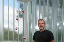 """Artist Tony Feher with one of his works, """"(Pinks)"""" during an exhibit at the Blaffer Art Museum in 2012."""