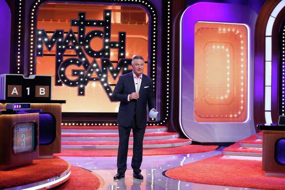 "Alec Baldwin, with telescoping mic in hand, hosts ""Match Game."""
