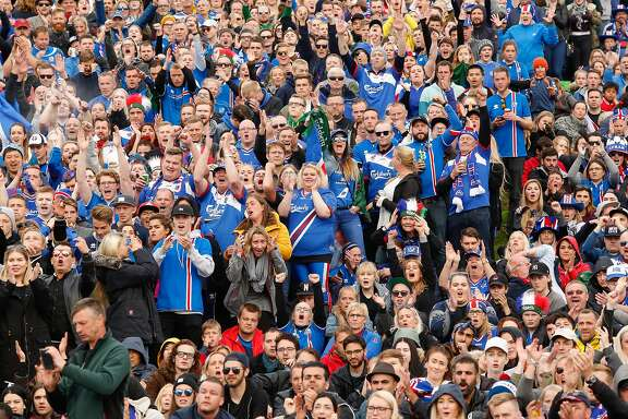 Icelandic soccer fans watch the Euro 2016 round of 16 match between Iceland and England on a large screen in Reykjavik, Iceland, Monday June 27, 2016.  Iceland pulled off the shock of the European Championship by beating England 2-1 in the round of 16 on Monday, continuing the improbable run of the smallest nation at the tournament. (AP Photo/Brynjar Gunnarsson)