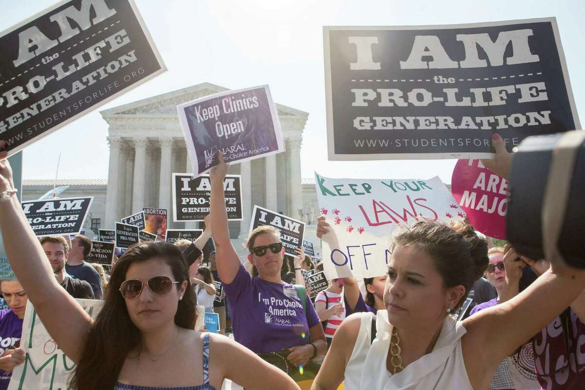 Pro-abortion rights and anti-abortion protesters rally in front of the U.S. Supreme Court in Washington, June 27, 2016. The court on Monday struck down parts of a restrictive Texas law that could have reduced the number of abortion clinics in the state to about 10 from what was once a high of roughly 40. (Zach Gibson/The New York Times)