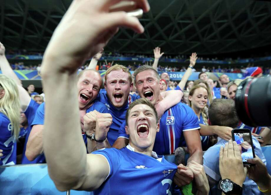 Iceland's Haukur Heidar Hauksson takes a selfie with supporters at the end of the Euro 2016 round of 16 soccer match between England and Iceland, at the Allianz Riviera stadium in Nice, France, Monday, June 27, 2016. (AP Photo/Claude Paris) Photo: Claude Paris, Associated Press / AP