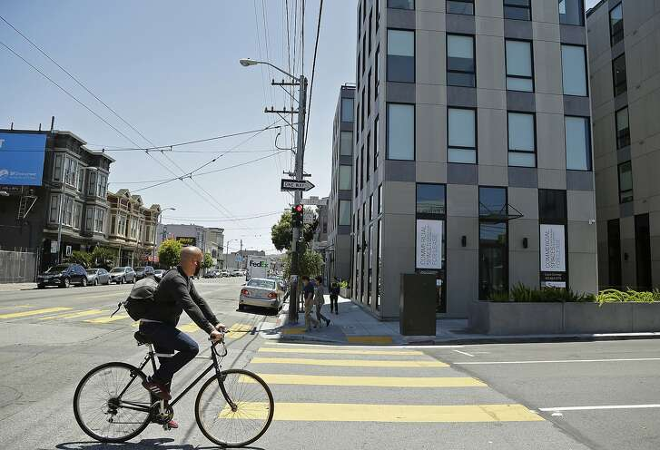 FILE -- In this June 2, 2015 file photo a man rides his bike past a new 40-unit Mission District condominium development in San Francisco. Rental rates, especially in the trendier parts of the city run well over $3,000 a month for a one-bedroom flat and nearly $5,000 for two bedrooms. California Gov. Jerry Brown and Democratic Legislative leaders reached a budget compromise, Thursday, that provides $400 million for low cost housing, as long as lawmakers approve Brown's proposal to allow developers to sidestep the local review process if their projects already meet neighborhood zoning requirements (AP Photo/Eric Risberg,file)