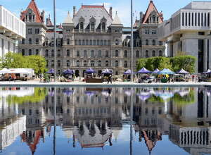 The Capitol and the Empire State Plaza farmer's market can be seen in one of the reflecting pools Wednesday May 18, 2016 in Albany, NY.  (John Carl D'Annibale / Times Union)
