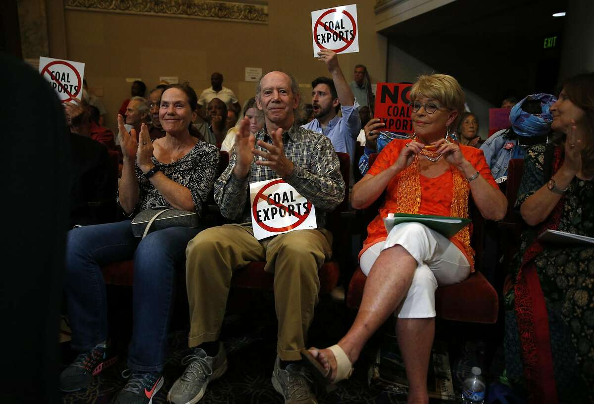Jeffery Kahn (center) applauds a speaker as he joins others against a proposed coal facility during Oakland City Council meeting in Oakland, Calif., on Monday, June 27, 2016.