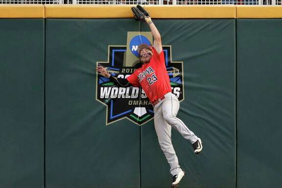 Arizona right fielder Zach Gibbons goes high at the wall to catch a flyball hit by Coastal Carolina's Michael Paez in the eighth inning.