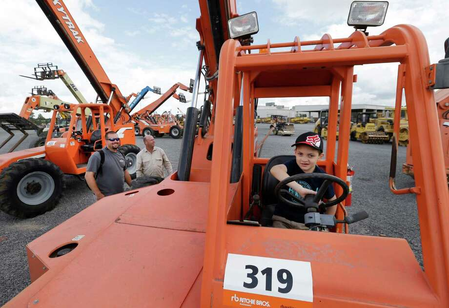 Clayton Hartman, 8, of Magnolia sits in the drivers seat of a telescopic lift as his dad, Joe Hartman, left, and George Hosford look at equipment during an auction at Ritchie Bros. Auctioneers, 15500 Eastex Freeway, Wednesday, June 22, 2016, in Humble.  ( Melissa Phillip / Houston Chronicle ) Photo: Melissa Phillip, Staff / © 2016 Houston Chronicle