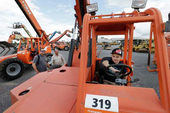 Clayton Hartman, 8, of Magnolia sits in the drivers seat of a telescopic lift as his dad, Joe Hartman, left, and George Hosford look at equipment during an auction at Ritchie Bros. Auctioneers, 15500 Eastex Freeway, Wednesday, June 22, 2016, in Humble.  ( Melissa Phillip / Houston Chronicle )