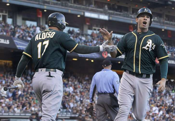 Oakland Athletics' Danny Valencia, right, is congratulated by Yonder Alonso after scoring against the San Francisco Giants during the second inning of an interleague baseball game in San Francisco, Monday, June 27, 2016. (AP Photo/Jeff Chiu)