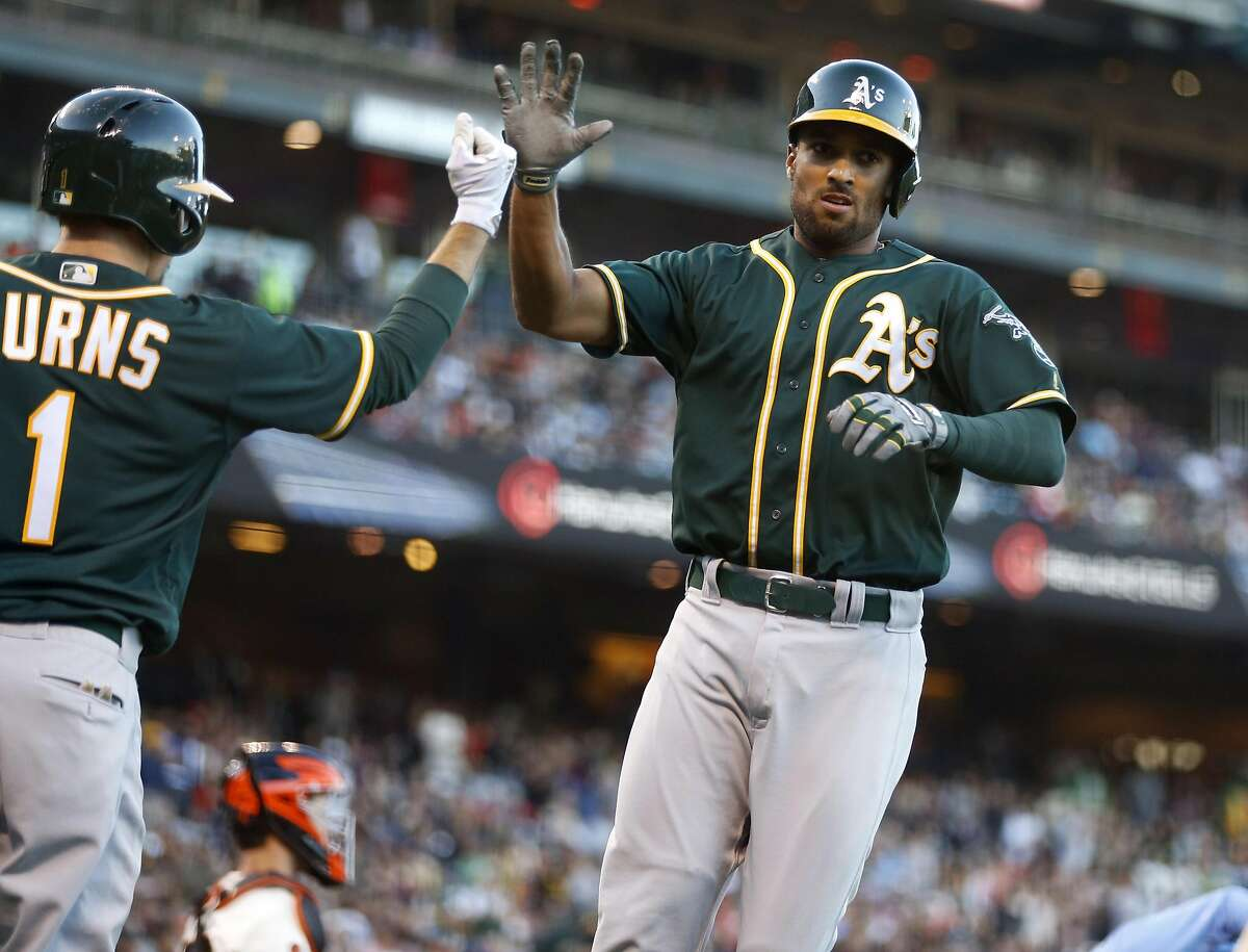 Marcus Semien high-fives Billy Burns after Semien hit a three-run home run against the Giants during the second inning on Monday, June 27, 2016, at AT&T Park in San Francisco.