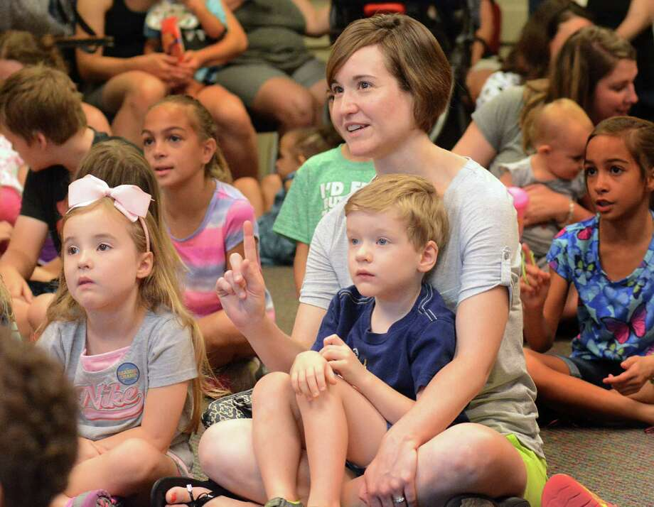 Amanda Ardill and her children, Annive and Liam, listen to Captain Book's Story Treasures during the pre-teen summer reading program at the George and Cynthia Woods Mitchell Library in The Woodlands. Photo: Z-David Hopper