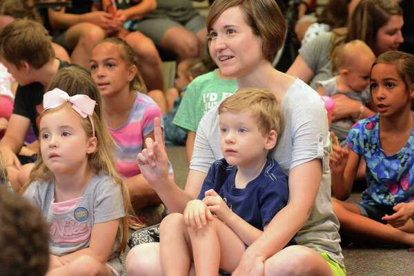 Amanda Ardill and her children, Annive and Liam, listen to Captain Book's Story Treasures during the pre-teen summer reading program at the George and Cynthia Woods Mitchell Library in The Woodlands.