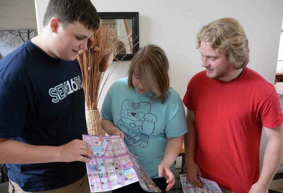 College Park High School students Nicholas Vessell, left, and Connor Kaminski, right, get tips on reading a Japanese railroad map from Laura DiRose, who is making her third trip to Japan. Photo: Z-David Hopper