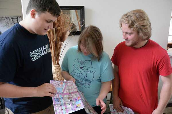 College Park High School students Nicholas Vessell, left, and Connor Kaminski, right, get tips on reading a Japanese railroad map from Laura DiRose, who is making her third trip to Japan.