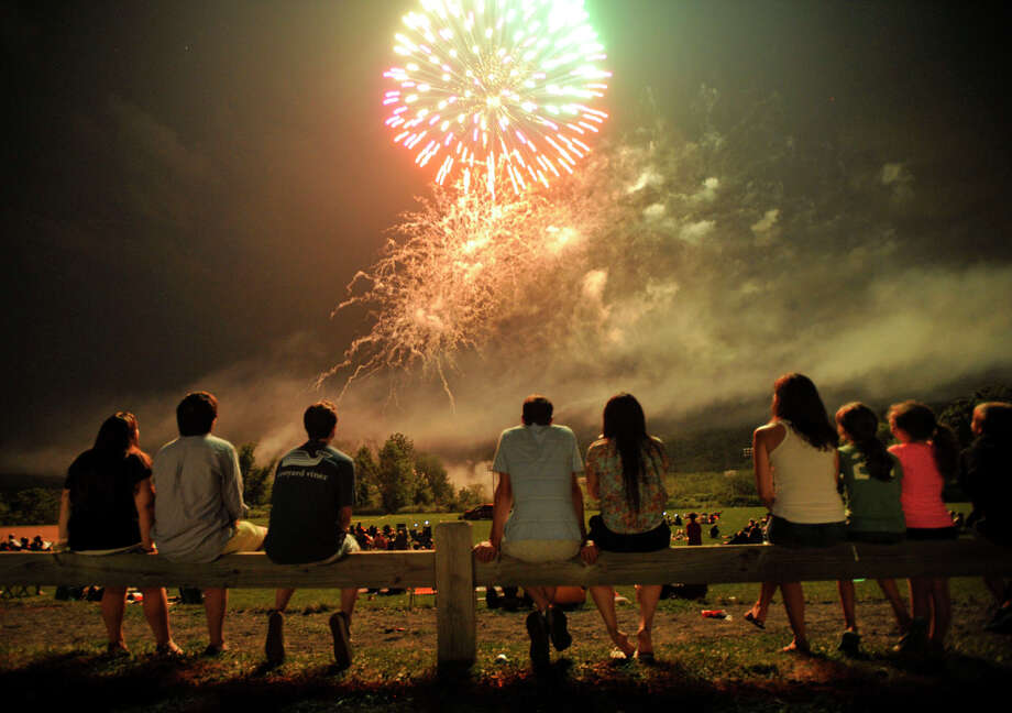 Onlookers take in the Ridgefield fireworks show at Ridgefield High School on Wednesday, July 4, 2012. Photo: Jason Rearick / Jason Rearick / The News-Times