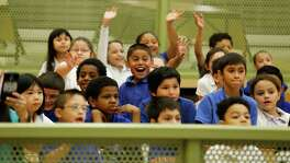 FILE PHOTO — Second grade students from SAISD's Mission Academy wave to members of Cos 4 A Cause during a school rally to award students on Thursday, May 14, 2015. Cos 4 A Cause is an organization of people who dress up as various comic culture characters and espouse positive attributes about life, society and education. (Kin Man Hui/San Antonio Express-News)