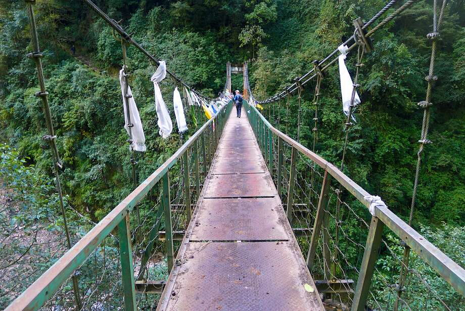 A wobbly suspension bridge, festooned with prayer flags, crosses a river on the trail to Dzongri in Sikkim. Photo: John Flinn, Special To The Chronicle