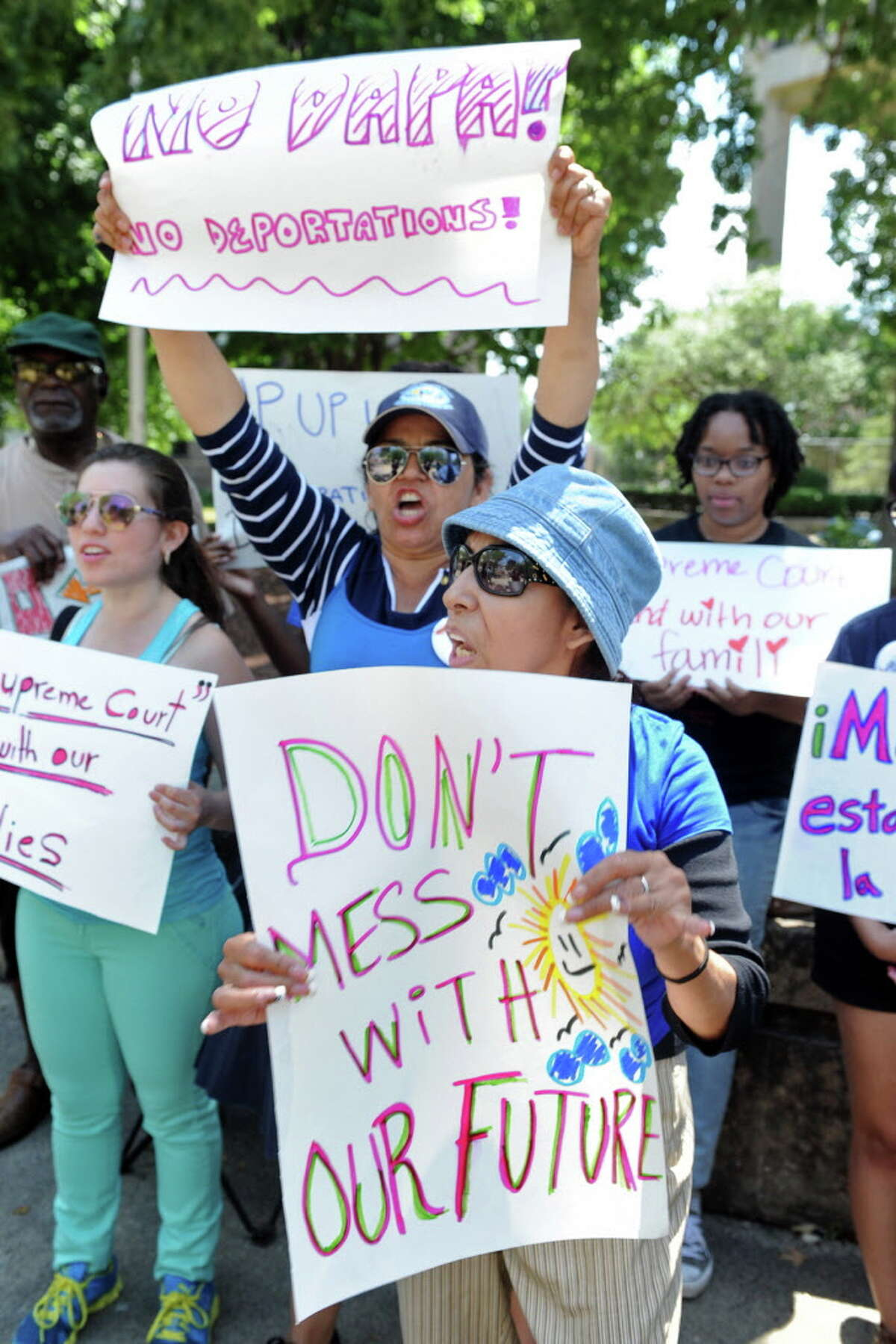 Maria Chumasero, front and center, and Maria Lima, back and center, both of Bridgeport, take part in a rally in front the Federal Courthouse, in Bridgeport, Conn. June 27, 2016. The rally was organized by local immigration advocacy groups in reaction to the Supreme Court?'s vote last week regarding Deferred Action for Parents of Americans.