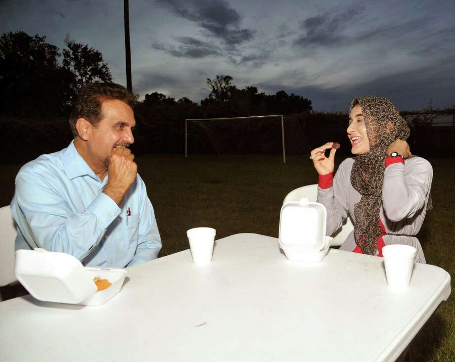 The Maryam Islamic Center director Anwer Wadiwala, left, and Fatima Loya each enjoy a date at the start of an evening meal during the monthlong celebration of Ramadan at the Sugar Land mosque. Photo: Eddy Matchette, Freelance / Freelance