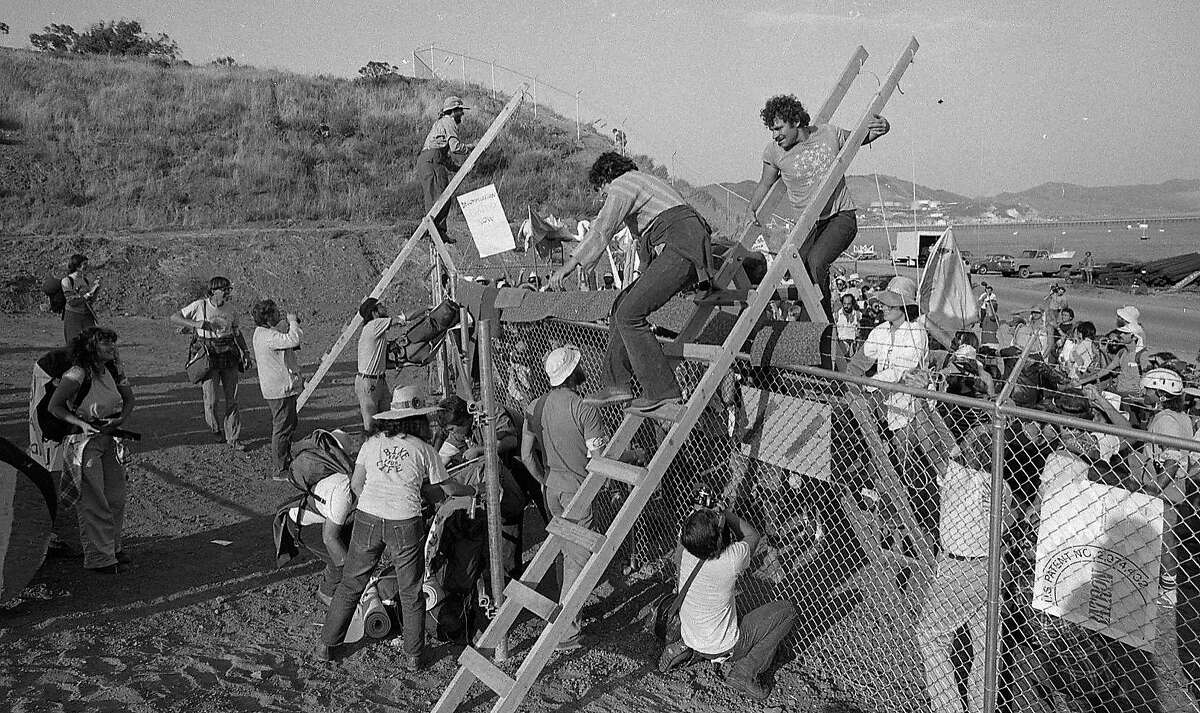 Demonstrators use ladders to climb over the fences in protests against the Diablo Canyon nuclear power plant, which would open seven years later, in 1985.