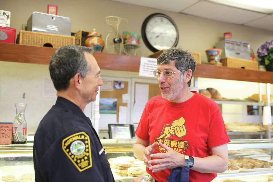 """Andy Pearce talks to Officer Cesar Ramirez about unsolicited phone calls during the inaugural Norwalk Police Department's """"Coffee with a Cop"""" opportunity to join police officers for coffee and conversation Tuesday at Muro's Italian Bakery. Photo: Danielle Robinson Calloway / For Hearst Connecticut Media / Connecticut Post Freelance"""