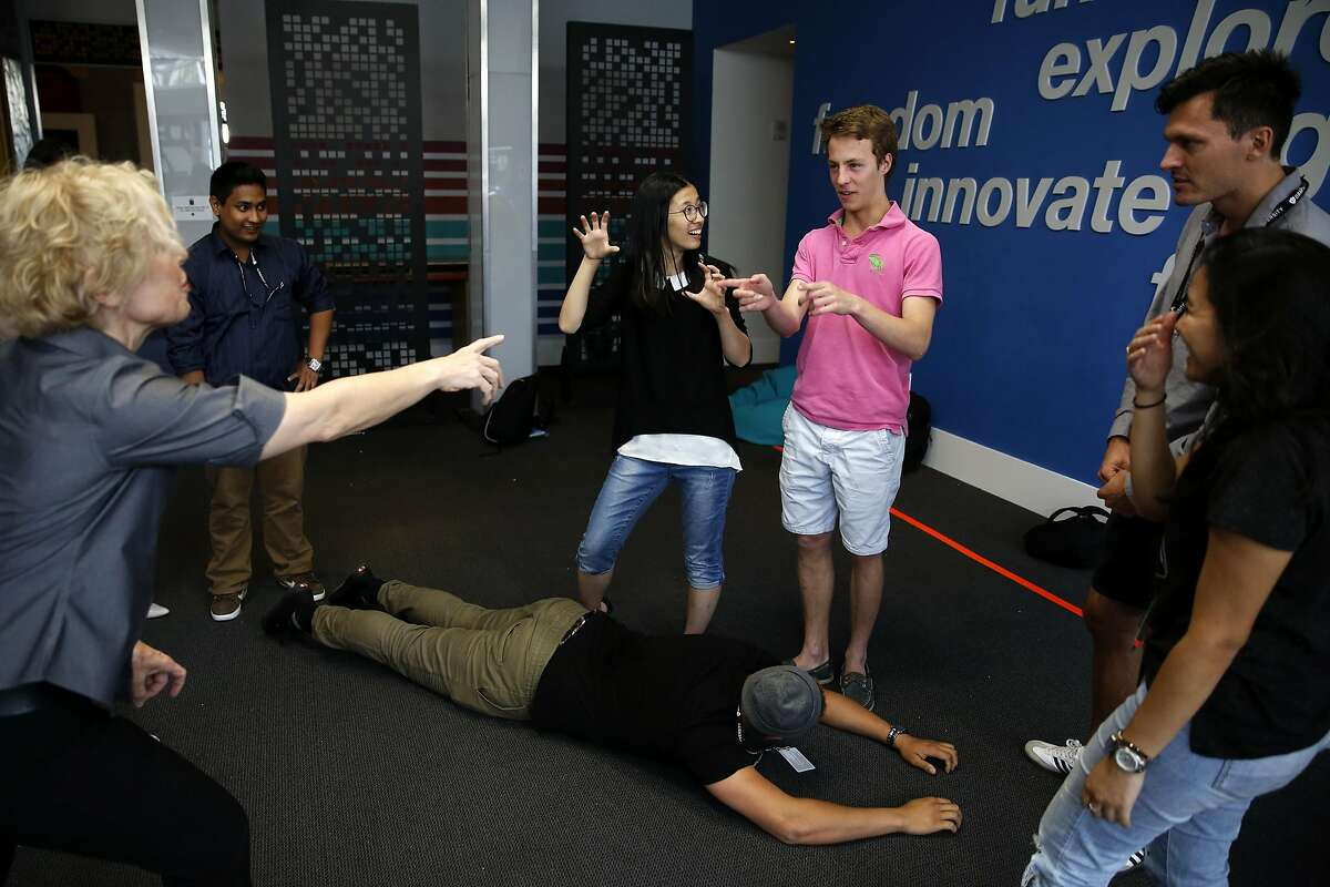 Instructor Diane Rachel (left) directs as Ajmal Jackson (center) lies on the ground pretending to be a boat and other students create a scene around him during an improv class at Draper University in San Mateo, California, on Monday, June 27, 2016.