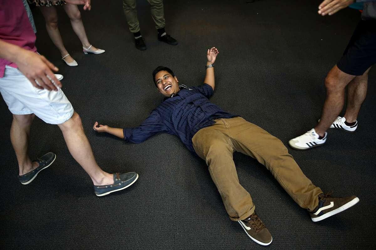 Buit Raj Thapa laughs while lying on the ground pretending to be water during an improv class at Draper University in San Mateo, California, on Monday, June 27, 2016.