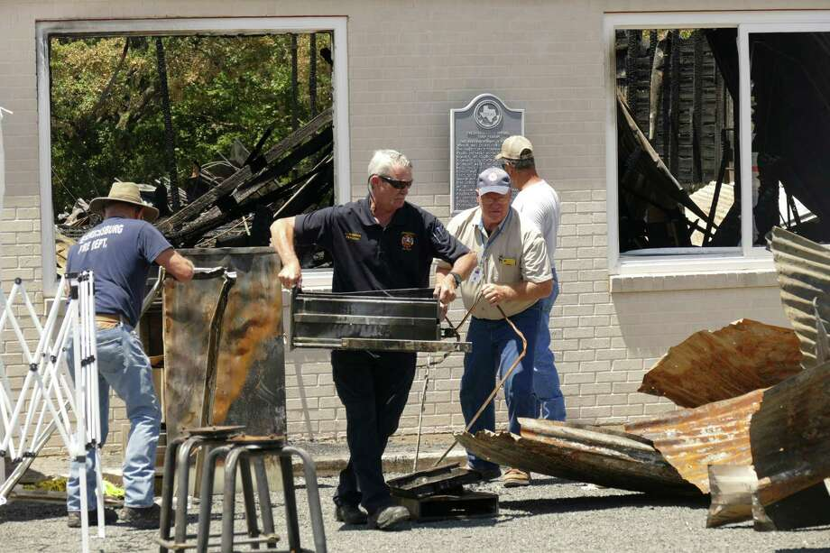 Fire chief Lynn Bissell carries a charred cabinet drawer at Turner Hall in Fredericksburg on June 21, which was destroyed by fire June 19. The building was the home of the Fredericksburg Social Turnverein, which was established in 1871 and moved to this location in 1909 and served as a community center and dance hall for generations. Police said Tuesday they believe the fire was set by a burglar. No arrests have been made. Photo: Billy Calzada /San Antonio Express-News / San Antonio Express-News