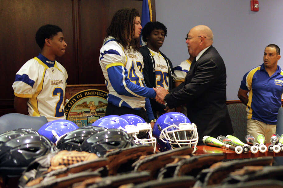 Harding High School football players shake hands with Police Chief A.J. Perez at a press conference announcing a $21,000 grant for sports equipment to be distributed across the city's schools. Photo: Cedar Attanasio / Hearst Connecticut Media / Connecticut Post