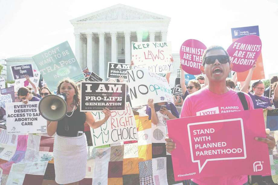 Pro-abortion rights and anti-abortion protesters rally in front of the U.S. Supreme Court in Washington, June 27, 2016. The court is expected to finish its term today with a decision on abortion é± a case deciding the constitutionality of two provisions of a Texas law regulating abortion could affect access to abortions for millions of women in several states. (Zach Gibson/The New York Times) Photo: ZACH GIBSON, STF / NYTNS