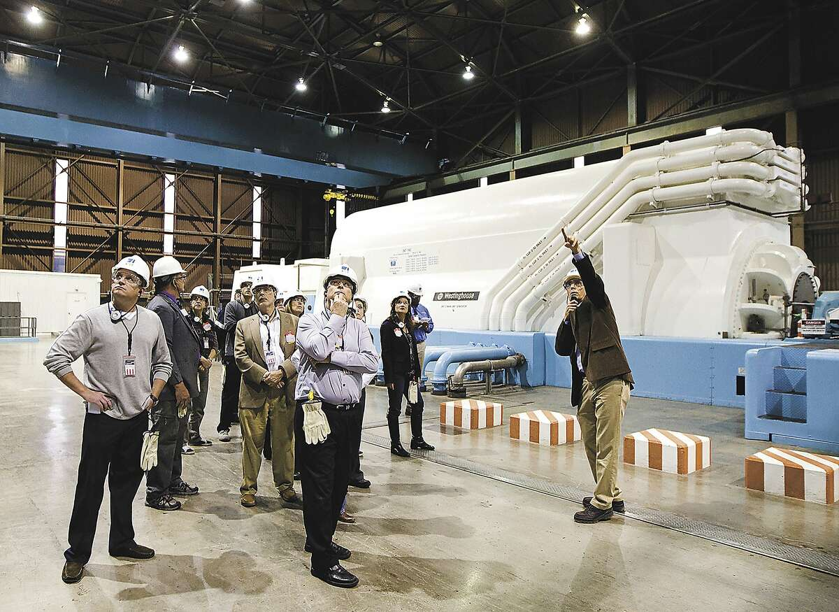 FILE - In this Jan. 9, 2013 file photo, station director Jim Welch, right, gives members of the California Coastal Commission and others a tour of the generator turbine deck of the Diablo Canyon nuclear power plant in San Luis Obispo, Calif. California regulators are expected to decide Tuesday, June 28, 2016, whether to drop their longstanding environmental objections to the state's last nuclear power plant in return for its promised early closing. (Joe Johnston/The Tribune (of San Luis Obispo) via AP, File) MANDATORY CREDIT