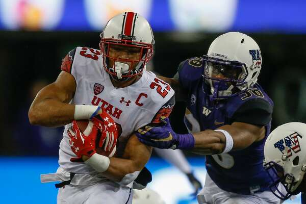 SEATTLE, WA - NOVEMBER 07:  Running back Devontae Booker #23 of the Utah Utes rushes against linebacker Azeem Victor #36 of the Washington Huskies on November 7, 2015 at Husky Stadium in Seattle, Washington. The Utes defeated the Huskies 34-23.  (Photo by Otto Greule Jr/Getty Images)