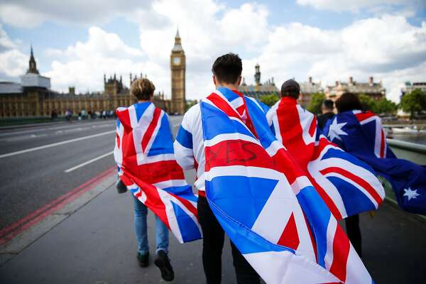 People walk over Westminster Bridge wrapped in Union flags, towards the Queen Elizabeth Tower (Big Ben) and The Houses of Parliament in central London on June 26, 2016.  Britain's opposition Labour party plunged into turmoil Sunday and the prospect of Scottish independence drew closer, ahead of a showdown with EU leaders over the country's seismic vote to leave the bloc. Two days after Prime Minister David Cameron resigned over his failure to keep Britain in the European Union, Labour leader Jeremy Corbyn faced a revolt by his lawmakers who called for him, too, to quit.  / AFP PHOTO / Odd ANDERSENODD ANDERSEN/AFP/Getty Images