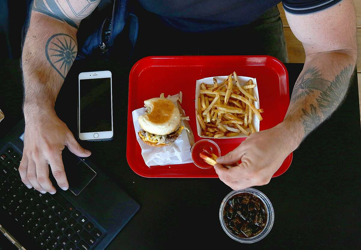 Thao Hill from San Francisco has a cheeseburger for lunch at Popsons on Tuesday, June 28, 2016, in San Francisco, Calif..