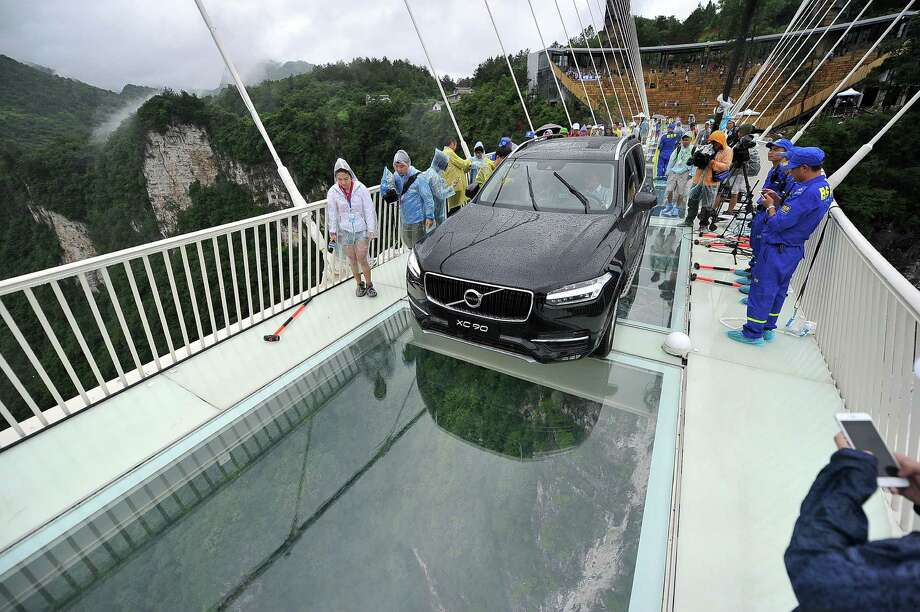 A car is driven across a glass-bottomed bridge in Zhangjiajie, China, as part of a demonstration of the bridge's safety. Photo: STR / Chinatopix