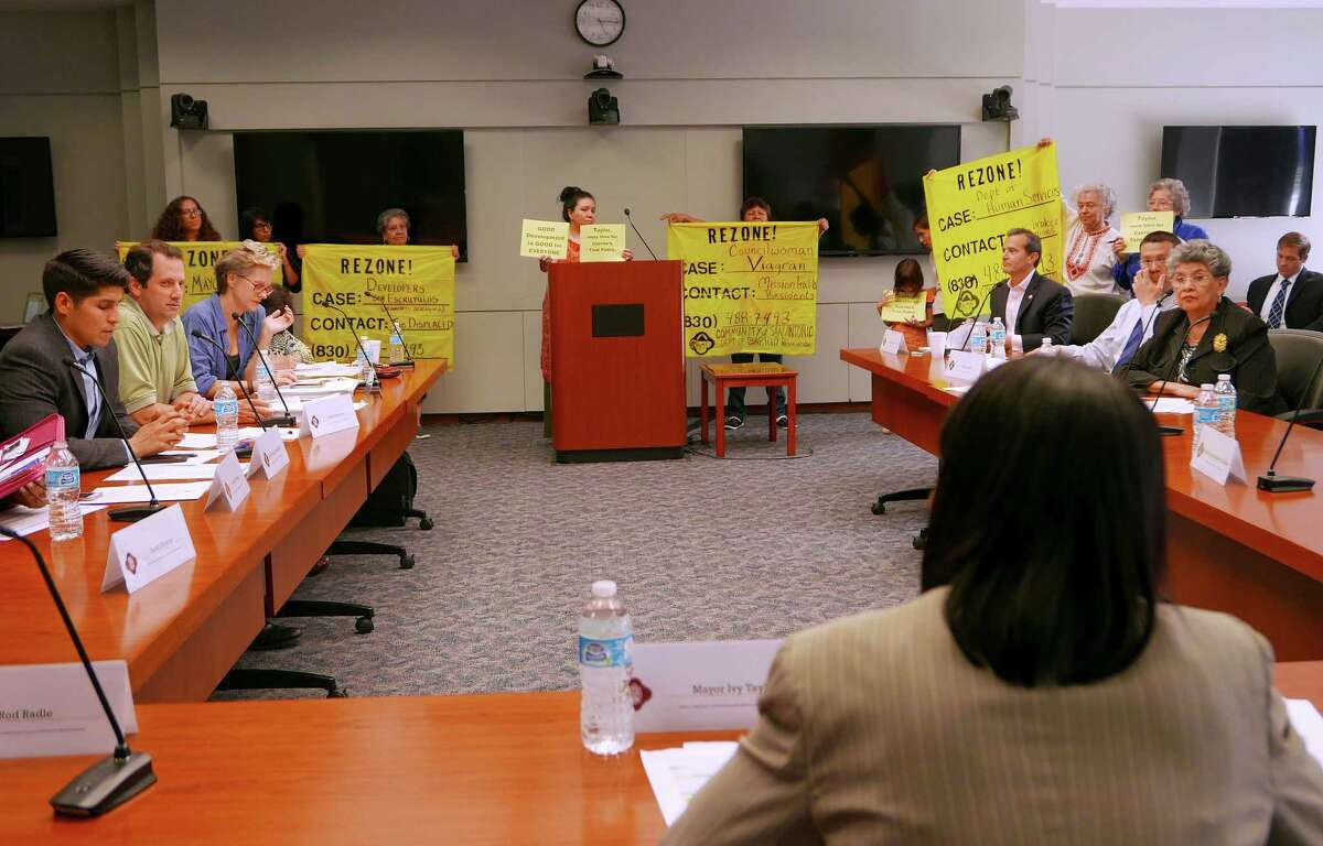 In April 2015, people upset about gentrification problems display signs as Mayor Ivy Taylor, foreground, speaks during a public meeting of the Mayor's Task Force on Preserving Dynamic and Diverse Neighborhoods. The group was formed after the displacement of hundreds of residents from the Mission Trails mobile home park.The committee met Tuesday to discuss how to add a housing bond to the ballot in May 2017.