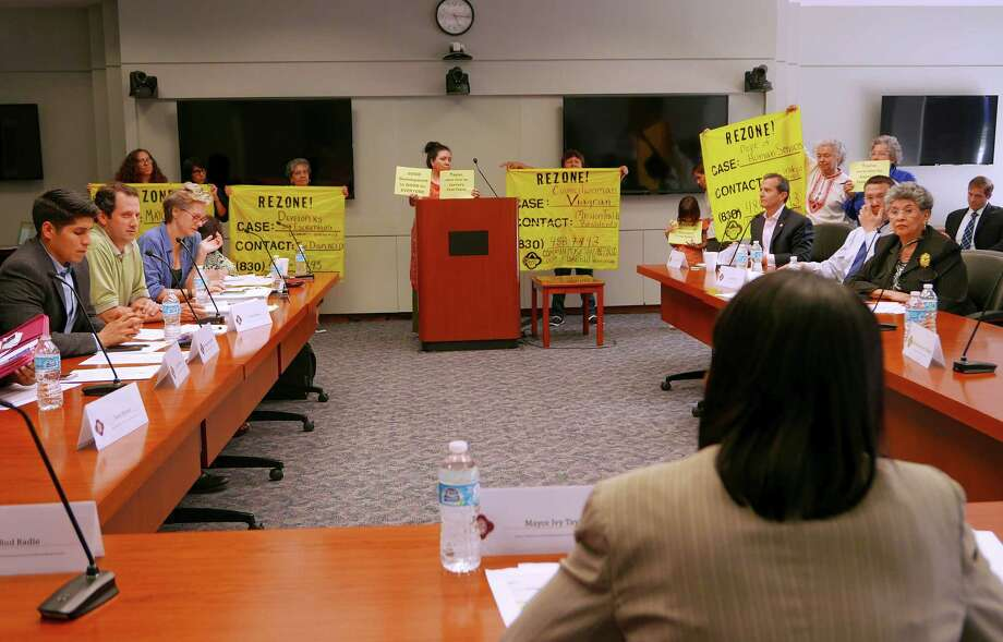 In April 2015, people upset about gentrification problems display signs as Mayor Ivy Taylor, foreground, speaks during a public meeting of the Mayor's Task Force on Preserving Dynamic and Diverse Neighborhoods. The group was formed after the displacement of hundreds of residents from the Mission Trails mobile home park.The committee met Tuesday to discuss how to add a housing bond to the ballot in May 2017. Photo: Billy Calzada /San Antonio Express-News / San Antonio Express-News