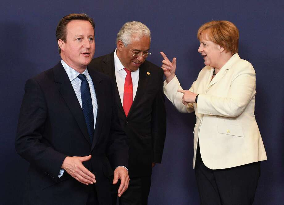 Britain Prime Minister David Cameron, left, gestures as Portuguese Prime Minister Antonio Costa talks with German Chancellor Angela Merkel in Brussels.  Photo: JOHN THYS, Stringer / AFP or licensors