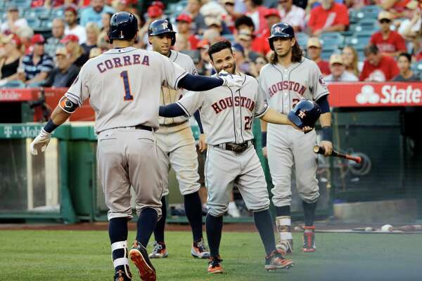 Houston Astros' Carlos Correa (1) is greeted by teammate Jose Altuve (27) after hitting a three-run home run during the first inning of a baseball game against the Los Angeles Angels Tuesday, June 28, 2016, in Anaheim, Calif. (AP Photo/Gregory Bull)
