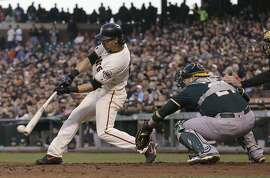 San Francisco Giants' Angel Pagan hits a two-run single in front of Oakland Athletics catcher Stephen Vogt during the fourth inning of a baseball game in San Francisco, Tuesday, June 28, 2016. (AP Photo/Jeff Chiu)
