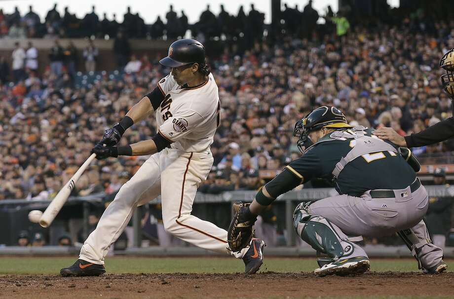 San Francisco Giants' Angel Pagan hits a two-run single in front of Oakland Athletics catcher Stephen Vogt during the fourth inning of a baseball game in San Francisco, Tuesday, June 28, 2016. (AP Photo/Jeff Chiu) Photo: Jeff Chiu, Associated Press