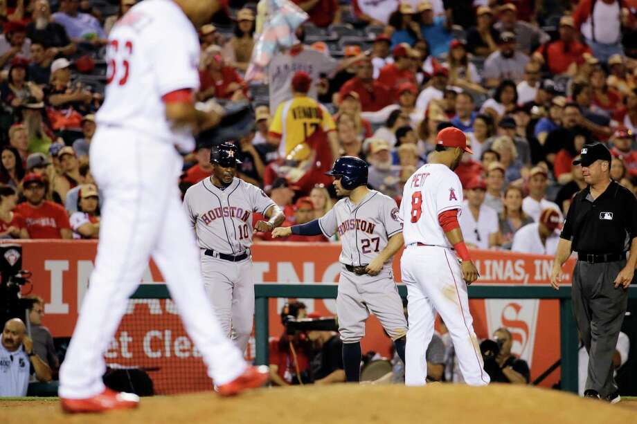 CORRECTS TO JOSE ALTUVE, INSTEAD OF MAX STASSI - Houston Astros' Jose Altuve (27) greets third base coach Gary Pettis (10) after stealing third base during the seventh inning of a baseball game against the Los Angeles Angels on Tuesday, June 28, 2016, in Anaheim, Calif. (AP Photo/Gregory Bull) Photo: Gregory Bull, Associated Press / Copyright 2016 The Associated Press. All rights reserved. This material may not be published, broadcast, rewritten or redistribu